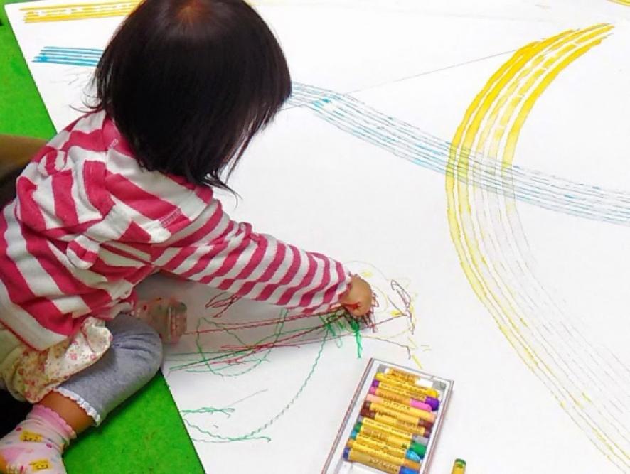 女の子がクレヨンでお絵描きしている